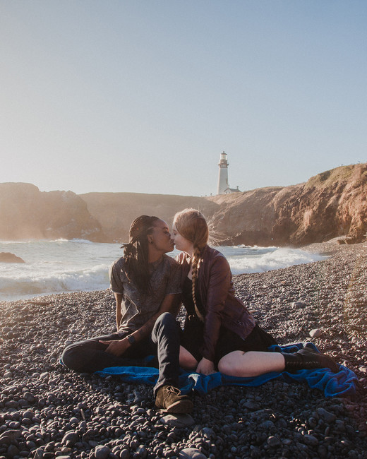 couple on rock beach engagement kiss