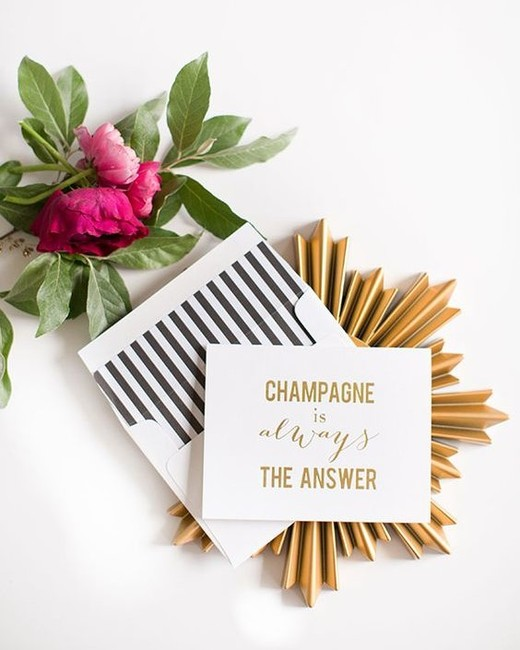 """white cardstock invites with gold writing """"Champagne is always the answer"""""""
