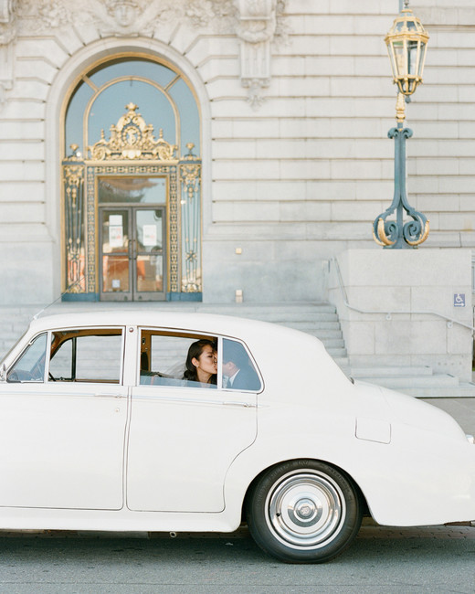bride and groom sitting in back of white vintage getaway car