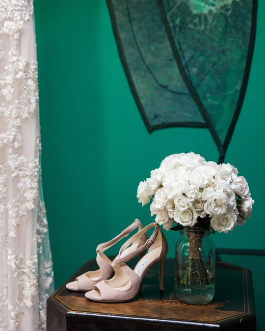 brides wedding shoes and white rose bouquet in glass jar