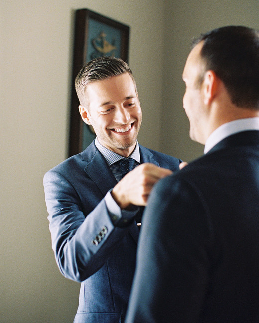 groom helping husband with tie