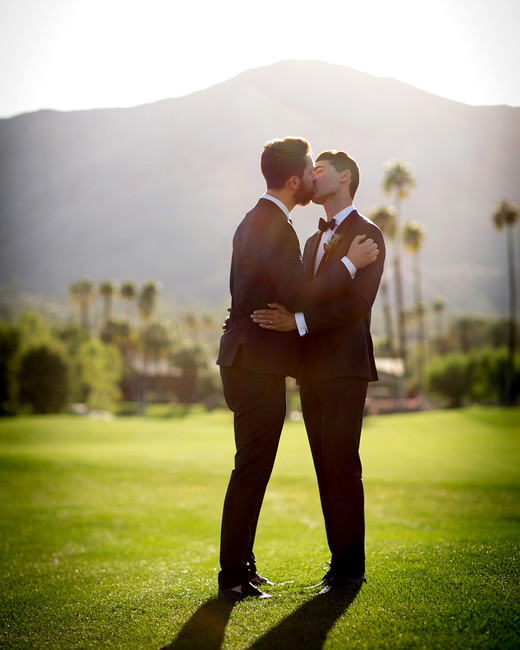 grooms kiss with mountain backdrop