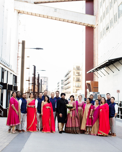 large wedding party wearing red, fuchsia, navy, and gold attire