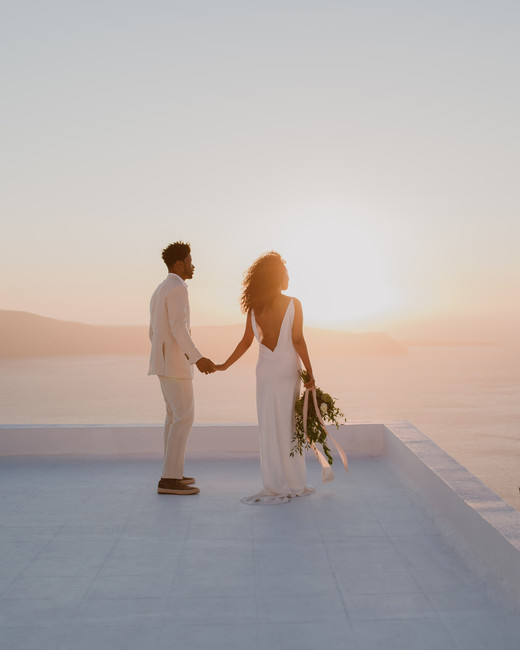 sunset wedding photos bride and groom holding hands on rooftop in greece