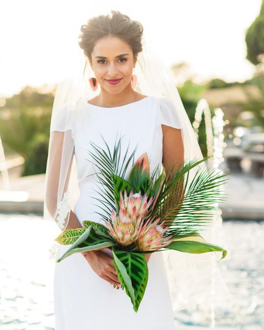 bride holding tropical leaf wedding bouquet