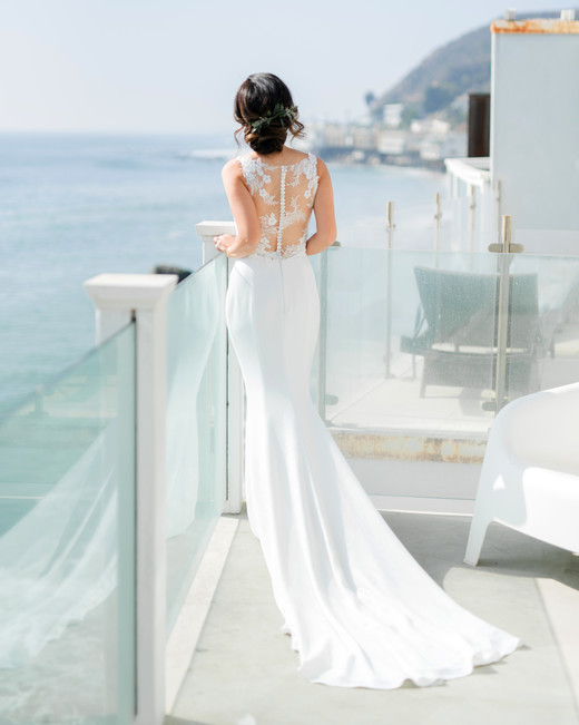destination wedding dress detailed back at railing on water
