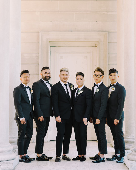 grooms standing with four groomsmen all wearing black suits