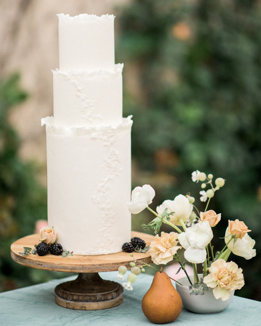 tall three tiered white frosted wedding cake