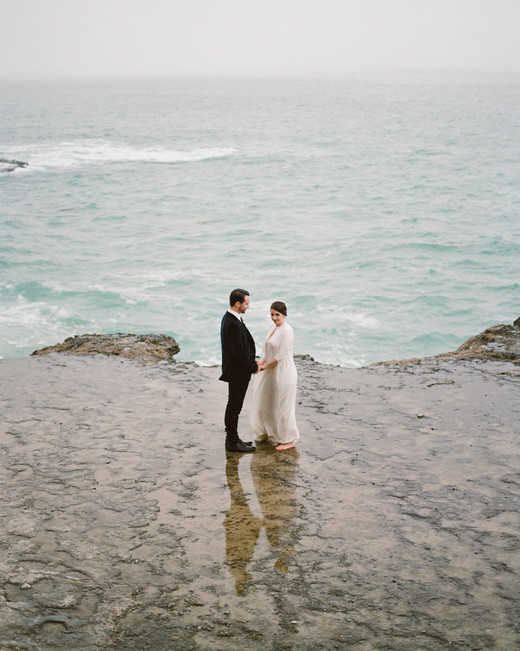 couple holding hands by water