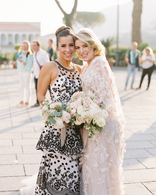 two ladies pose with flower bouquets