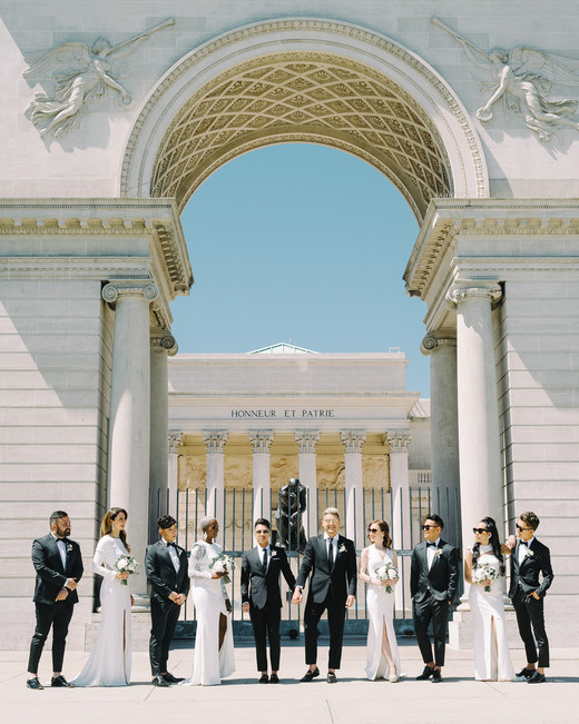 grooms with their wedding party outside of city hall