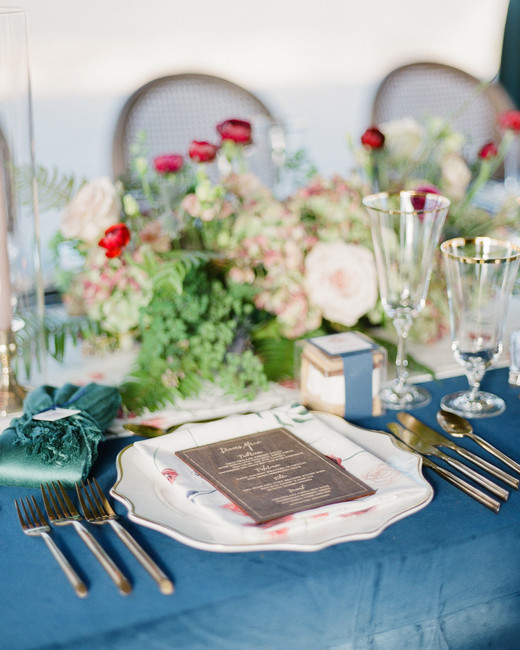 gold rimmed place settings and gold flatware on blue table linens