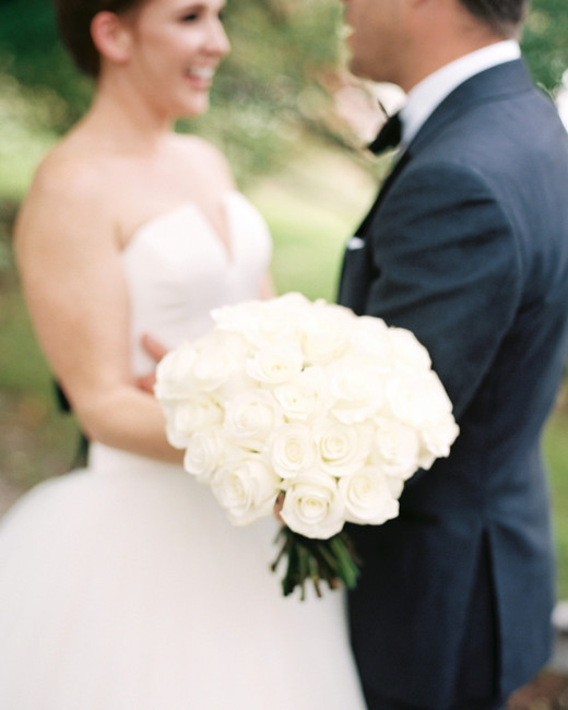 single flower wedding bouquet white roses held by bride embracing groom