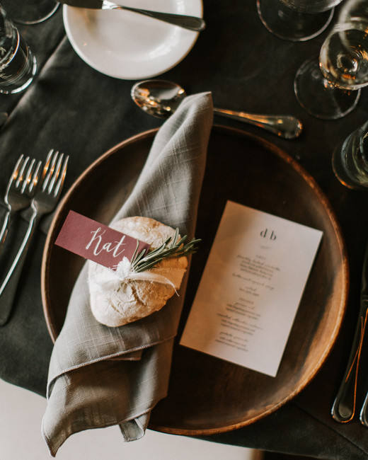 natural wood plates with light gray napkins and burgundy placecards