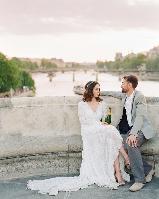 sunset wedding photos bride and groom sitting with champagne in paris
