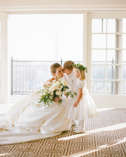 bride kneeling down next to flower girl and ring bearer