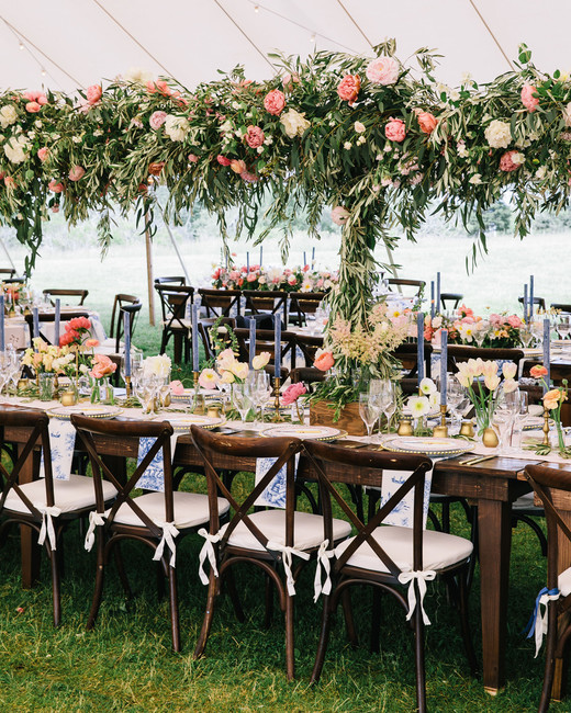 wooden long reception table with pink and white floral arrangements and white linens