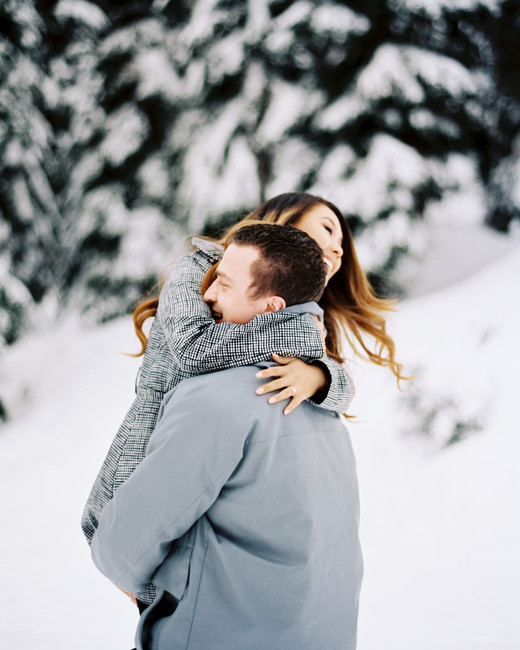 man carrying woman snow