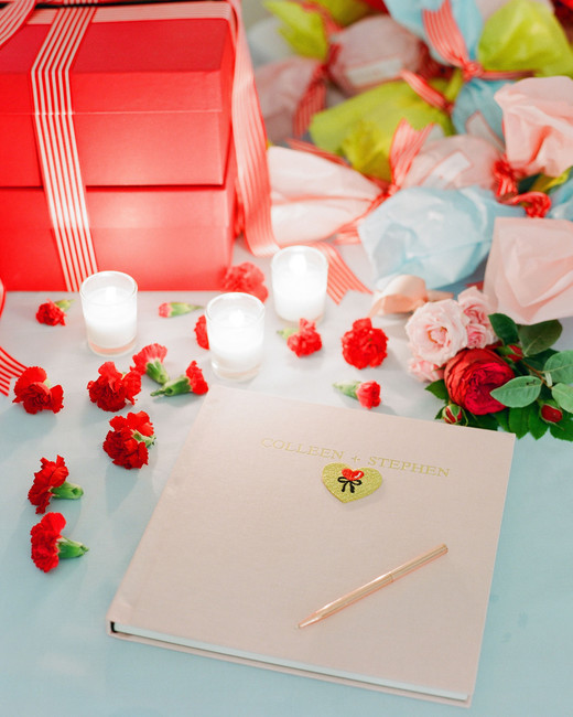 colleen stephen newport wedding guestbook surrounded by candles and red carnations