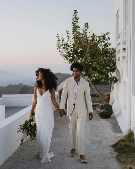 elopement outfit inspiration couple holding hands outside of white santorini venue