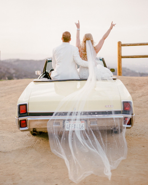 sunset wedding photos bride and groom in getaway car overlooking los angeles