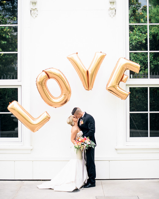 Bride and groom standing under gold L-O-V-E balloons