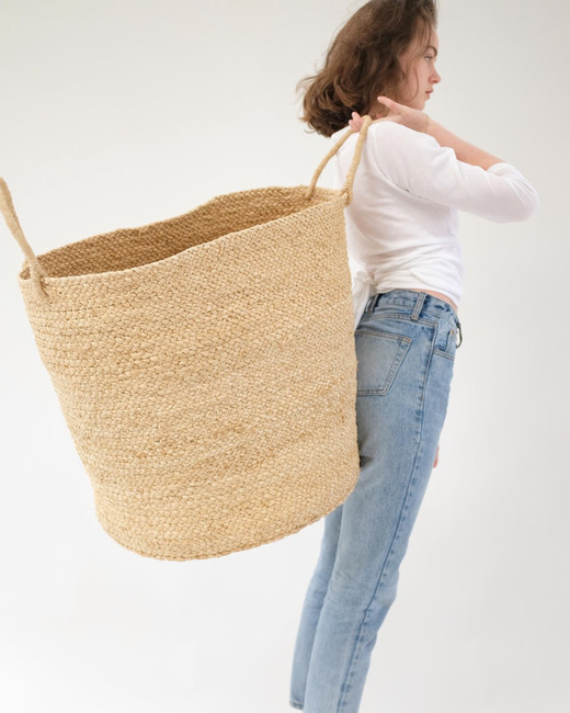 woman holding large woven storage basket