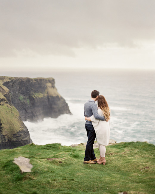 destination engagement couple ocean view over rock cliff