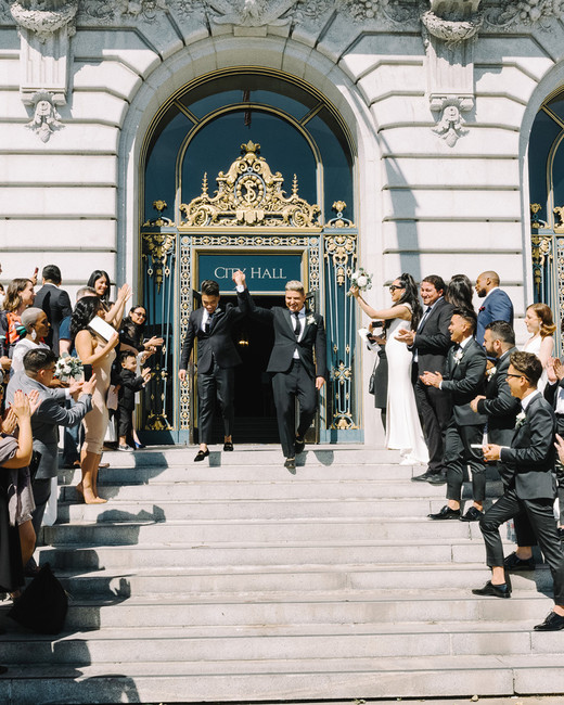 grooms walking out of city hall after wedding ceremony