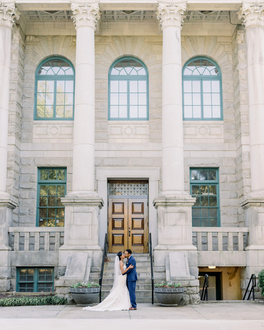 city hall wedding bride and groom kissing in front of building with arched windows and pillars