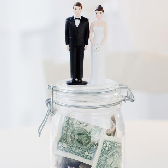 bride and groom figurines on money jar