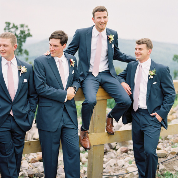 groom outdoors fence with groomsmen