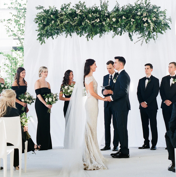 couple at religious wedding ceremony with greenery overhead