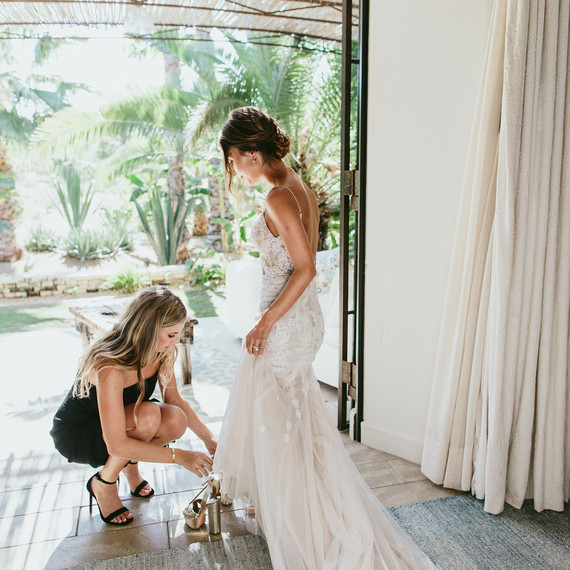 maid of honor helping bride with her shoes
