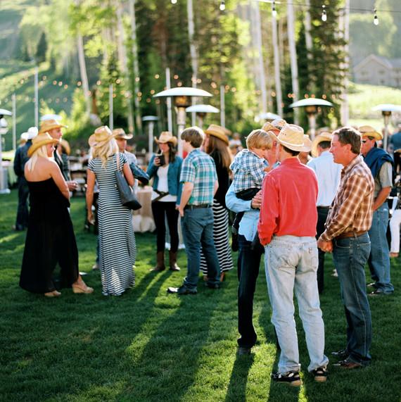 guests mingle outdoors cowboy hats