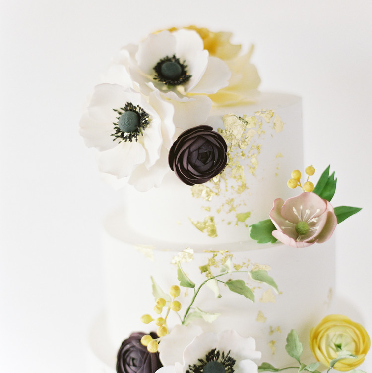 White Wedding Cake with Flowers and Gold Foil Details
